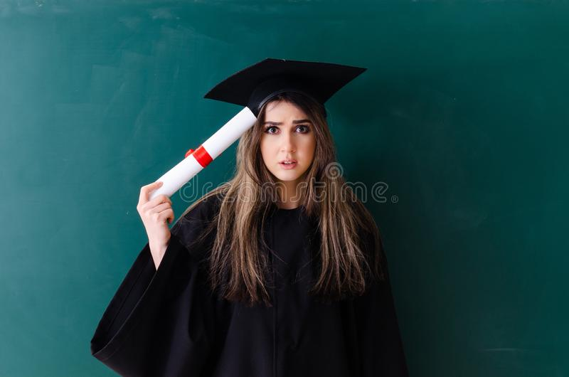 El estudiante de tercer ciclo de sexo femenino delante del tablero verde imagen de archivo libre de regalías