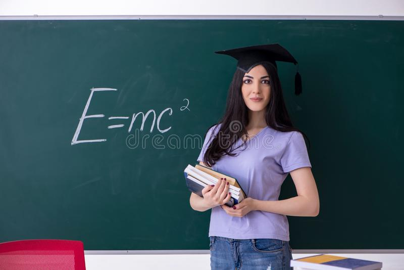 El estudiante de tercer ciclo de sexo femenino delante del tablero verde foto de archivo libre de regalías