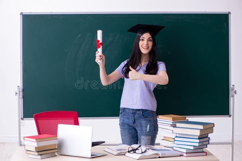 El estudiante de tercer ciclo de sexo femenino delante del tablero verde imágenes de archivo libres de regalías