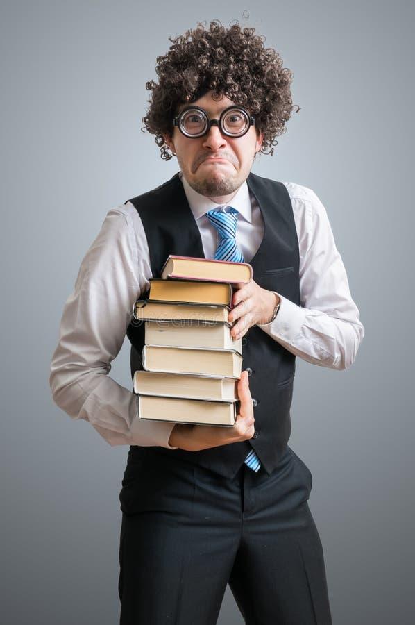 El estudiante divertido del empollón hiolding los libros foto de archivo