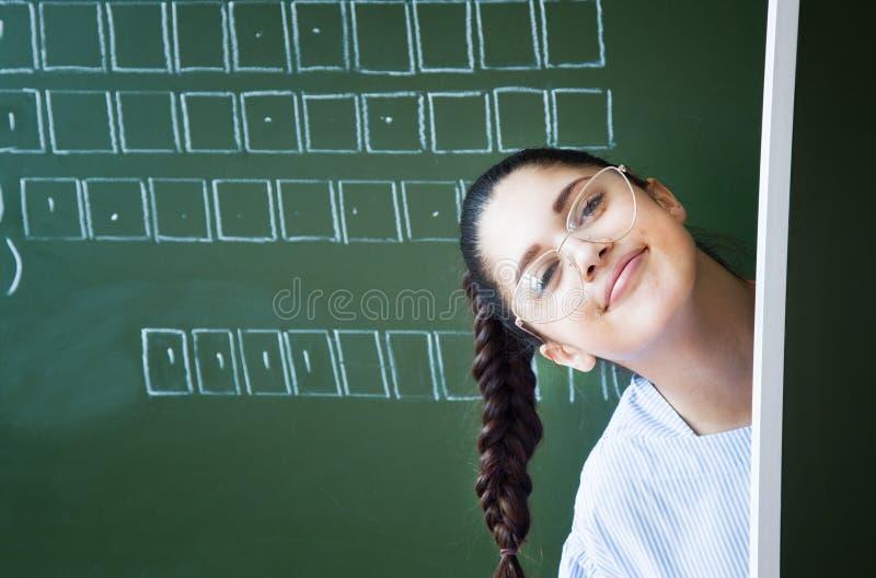 El estudiante en vidrios permanece la pizarra cercana en sala de clase imagenes de archivo