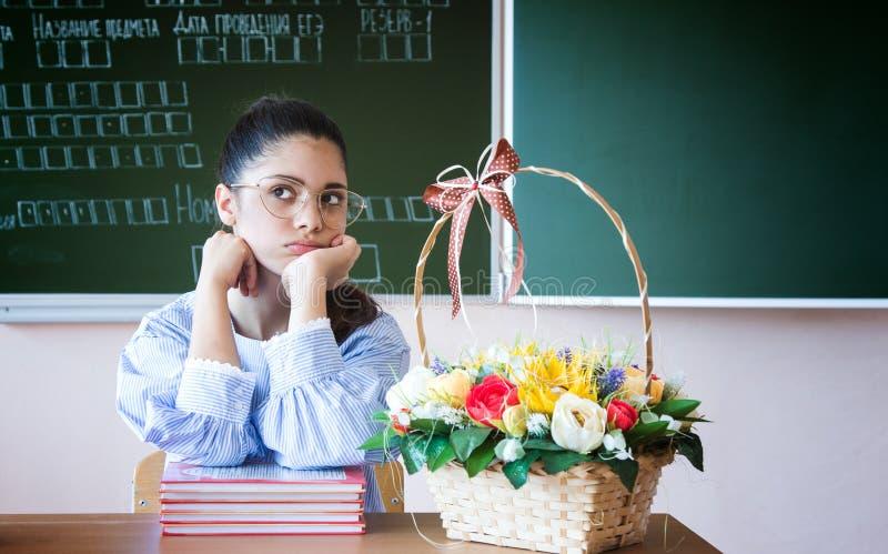 El estudiante en vidrios se sienta contra la pizarra y mira lejos en sala de clase imagenes de archivo