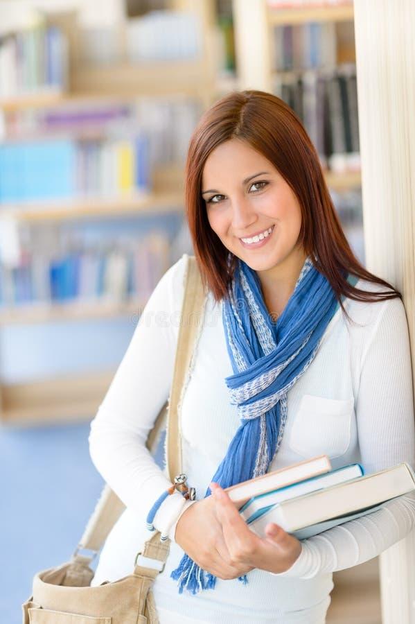 El estudiante femenino lleva los libros de la educación de la biblioteca imagen de archivo