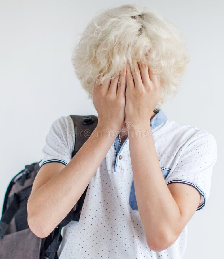 El estudiante frustrado cubrió su cara con sus manos imagen de archivo