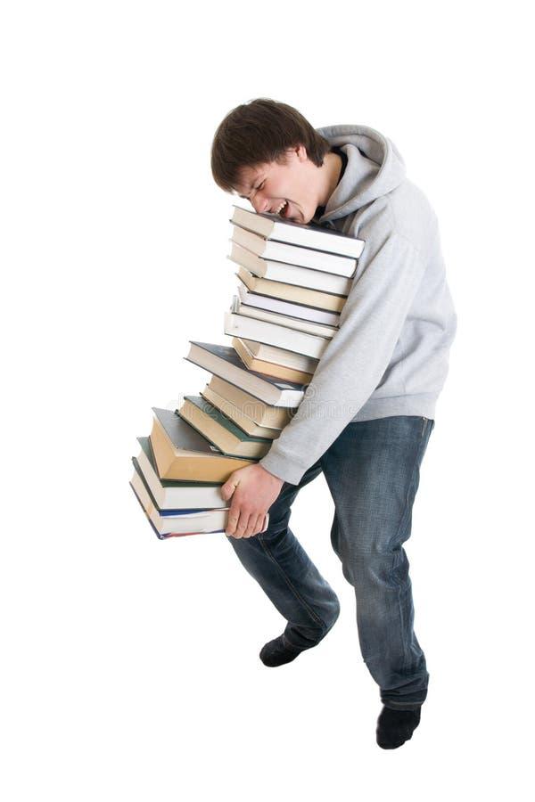 El estudiante joven con una pila de libros aislados imagen de archivo