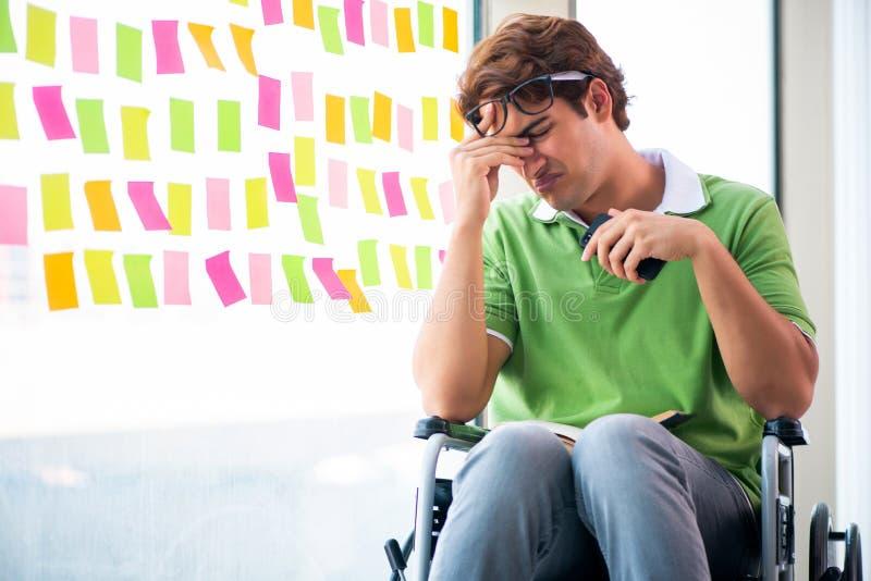 El estudiante joven en silla de ruedas con muchas prioridades en conflicto fotos de archivo