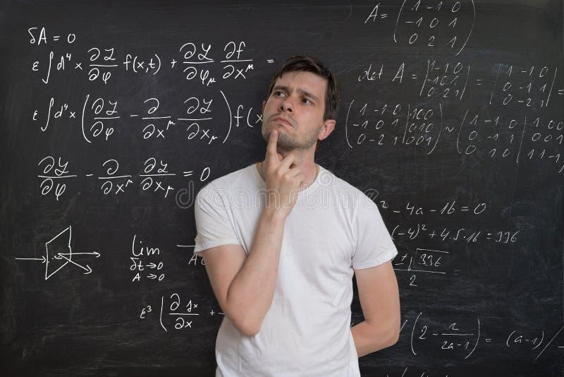 El estudiante joven es de pensamiento y que soluciona de problema matemático Formular de la matemáticas en la pizarra en fondo foto de archivo