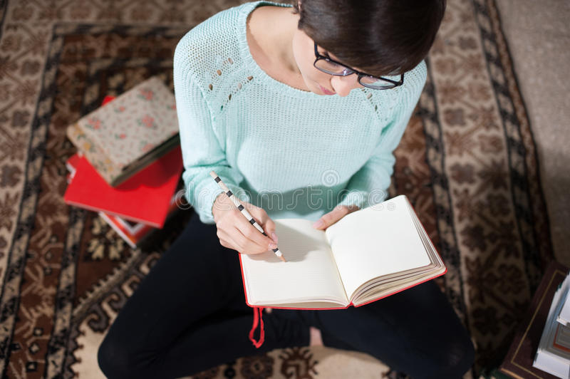 El estudiante joven que anota observa en casa fotos de archivo