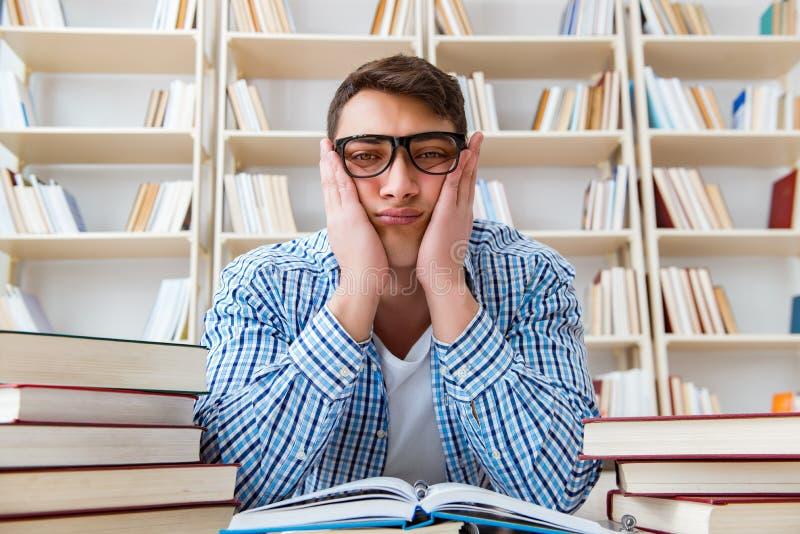 El estudiante joven que estudia con los libros fotografía de archivo