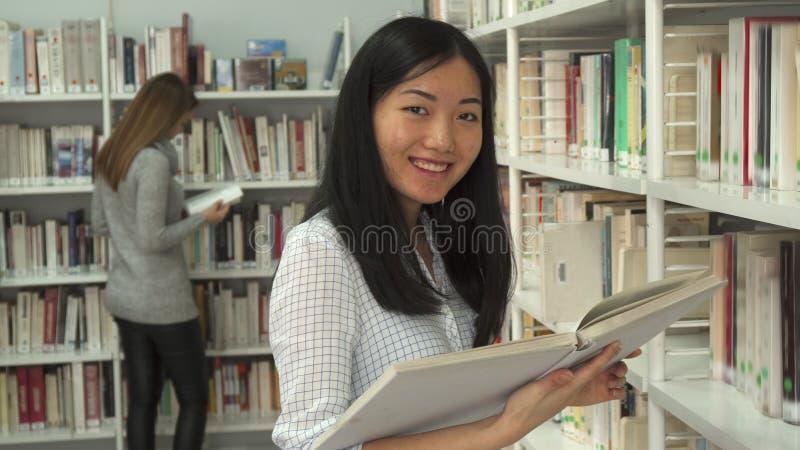 El estudiante lee el libro en la biblioteca fotos de archivo