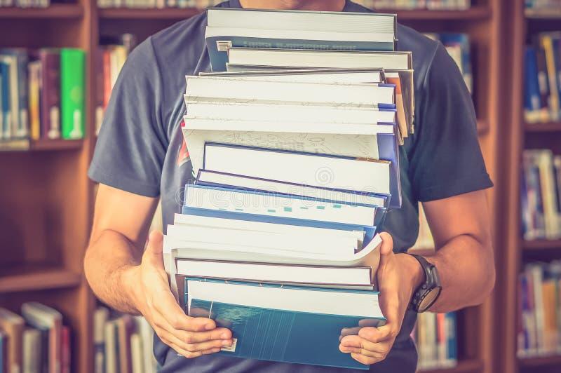 El estudiante lleva los libros en la biblioteca imagen de archivo
