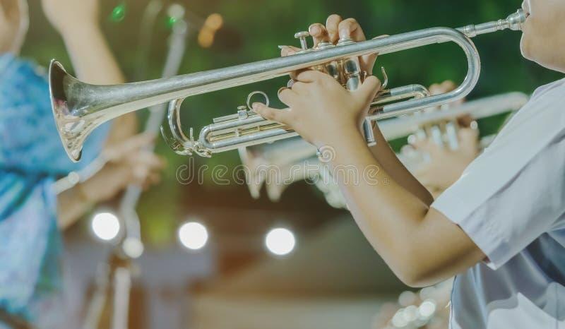 El estudiante masculino con los amigos sopla la trompeta con la banda para el funcionamiento en etapa foto de archivo libre de regalías