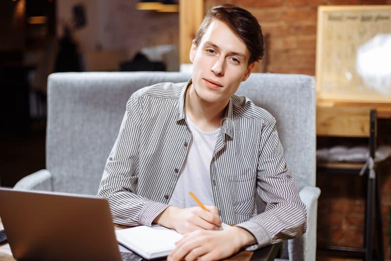El estudiante masculino joven escribe la información en un cuaderno, se prepara para las conferencias en el campus universitario, imagen de archivo libre de regalías