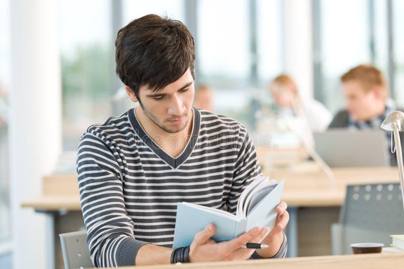 El estudiante masculino joven leyó el libro en sala de clase fotos de archivo