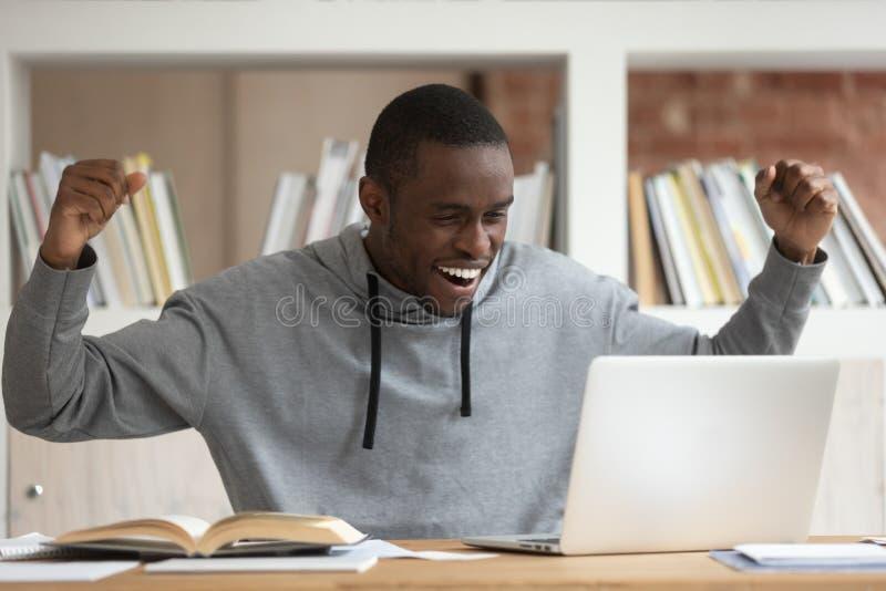 El estudiante masculino negro feliz consigue el correo electrónico agradable en el ordenador portátil imagen de archivo libre de regalías