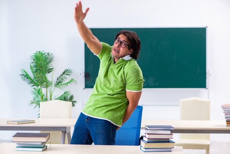 El estudiante masculino que sufre de impulso en la sala de clase foto de archivo libre de regalías