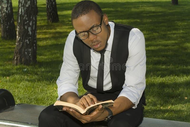 El estudiante negro lee un libro fotografía de archivo