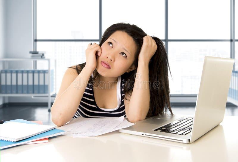 El estudiante o la mujer de negocios asiático chino cansó el trabajo y estudiar en el ordenador portátil del ordenador foto de archivo