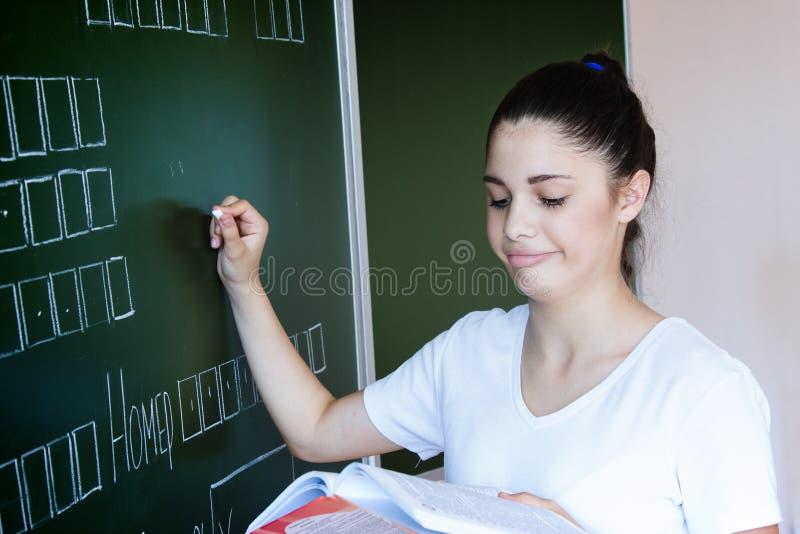 El estudiante permanece la pizarra cercana en sala de clase fotografía de archivo