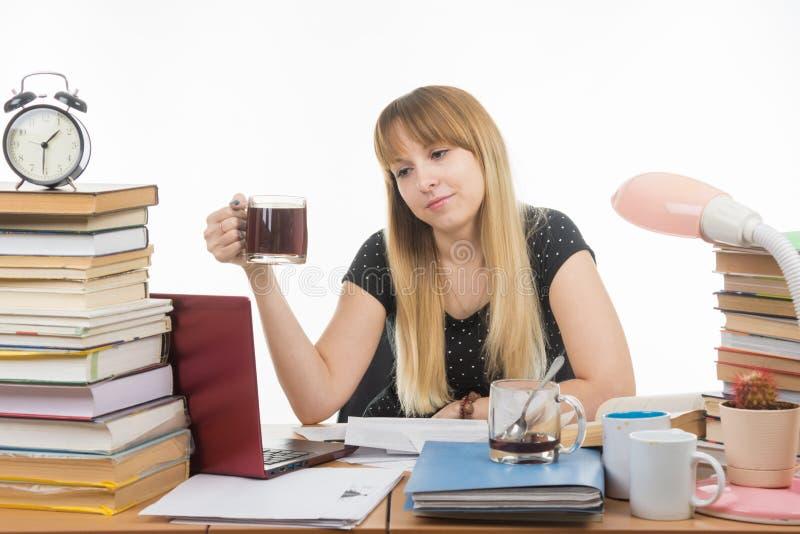 El estudiante prepara un proyecto de la tesis en la noche y bebió otra taza de café fotografía de archivo