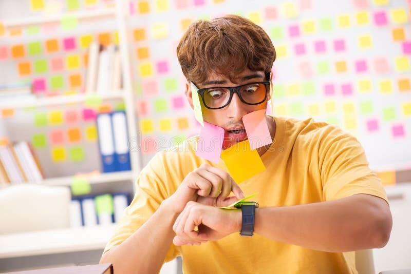 El estudiante que se prepara para los exámenes con muchas prioridades en conflicto foto de archivo libre de regalías