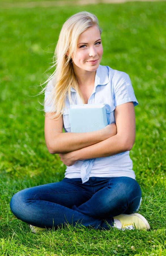 El estudiante que sostiene el libro se sienta en la hierba fotos de archivo