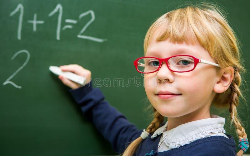 El estudiante trabaja en una sala de clase de la escuela, niño en la escuela, imagen de archivo