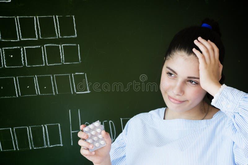 El estudiante trastornado con los piils permanece la pizarra cercana en sala de clase fotografía de archivo