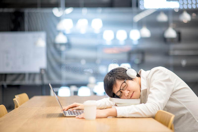 El estudiante universitario asiático joven toma una siesta en biblioteca fotos de archivo