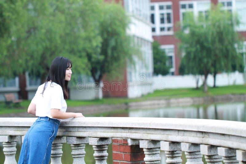 El estudiante universitario chino asiático disfruta de tiempo libre en el campus imagen de archivo