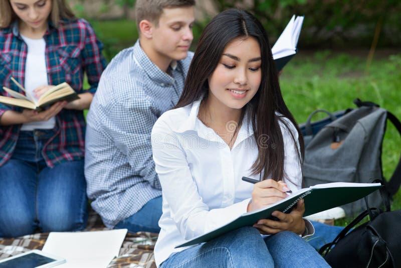 El estudiar asiático de la muchacha del estudiante, tomando notas en campus imagen de archivo libre de regalías
