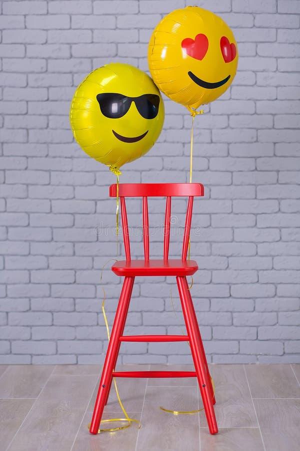 El estudio gris del apartamento con la silla, pared de ladrillo, los detalles amarillos hincha la silla del rojo del emoji imagen de archivo