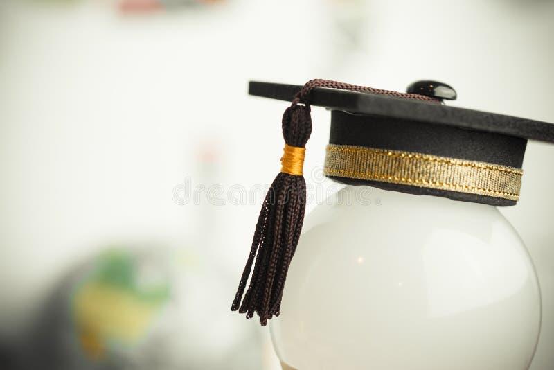 El estudio o el conocimiento graduado de la educación es concepto del poder: Casquillo graduado puesto en fondo de la bombilla bl foto de archivo