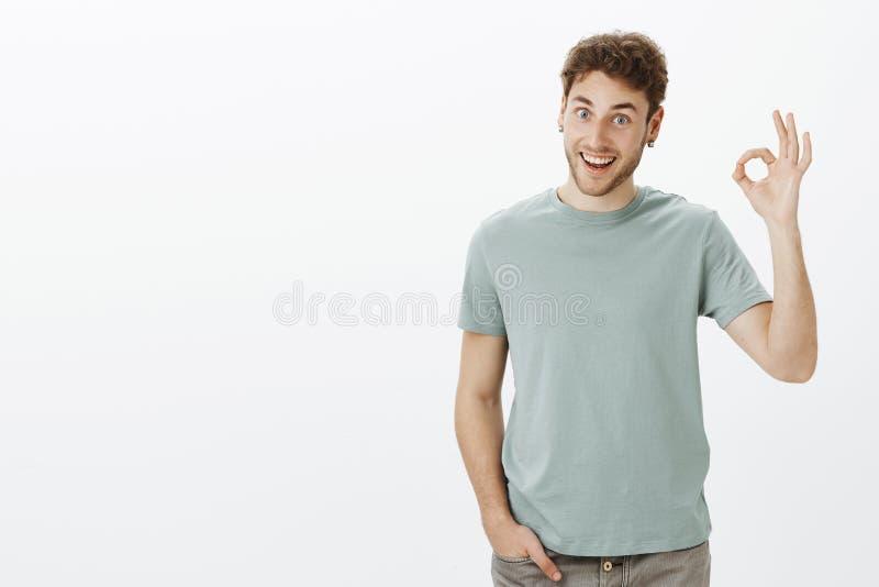 El estudio tiró de compañero de trabajo masculino europeo de amistoso-mirada divertido en camiseta de moda, aumentando la mano en imagen de archivo libre de regalías