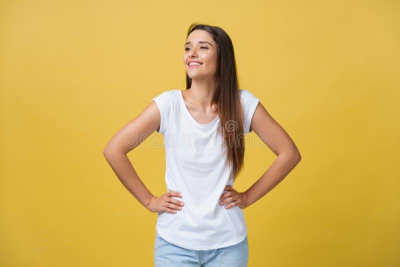 El estudio tiró de hembra joven segura de sí mismo atractiva en el gran humor que sentía feliz, llevando a cabo las manos en su c fotografía de archivo libre de regalías