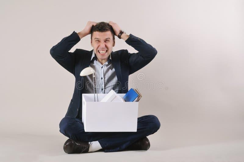 El estudio tiró de hombre de negocios enojado con la materia de la oficina en la caja si imágenes de archivo libres de regalías