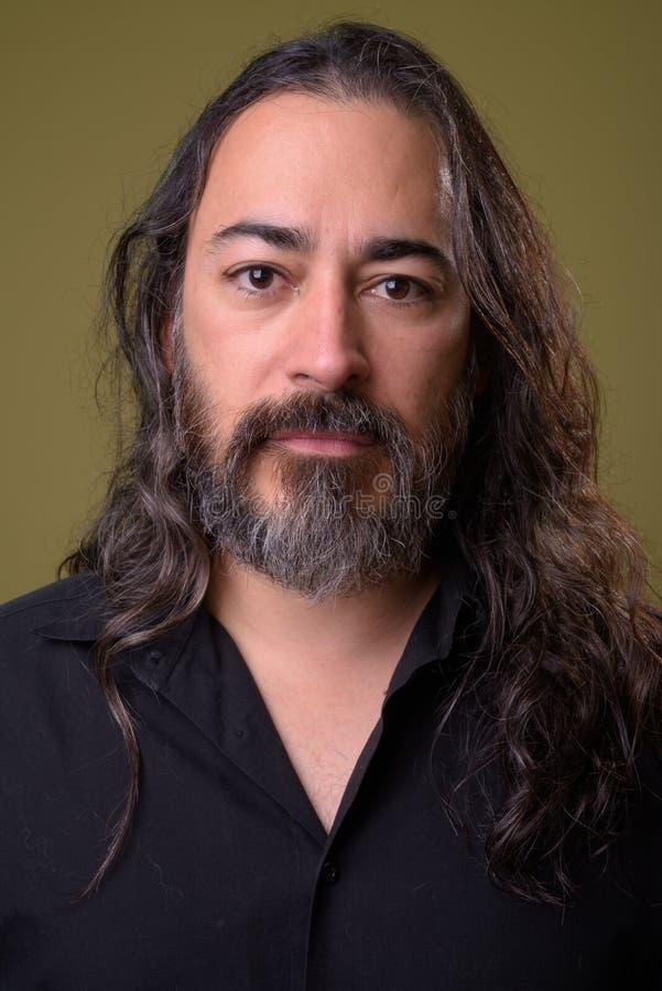 El estudio tiró de hombre de negocios multi-étnico barbudo hermoso maduro con el pelo largo imagen de archivo libre de regalías