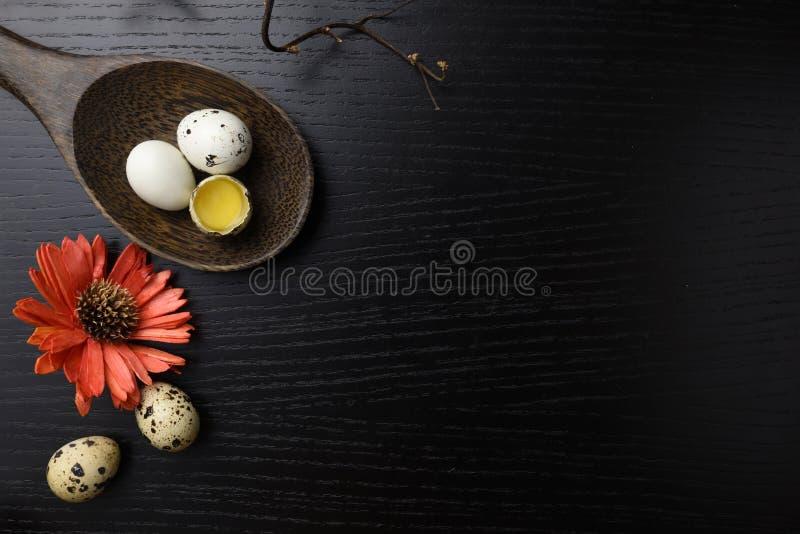 El estudio tiró de huevos en un fondo de madera negro imagen de archivo