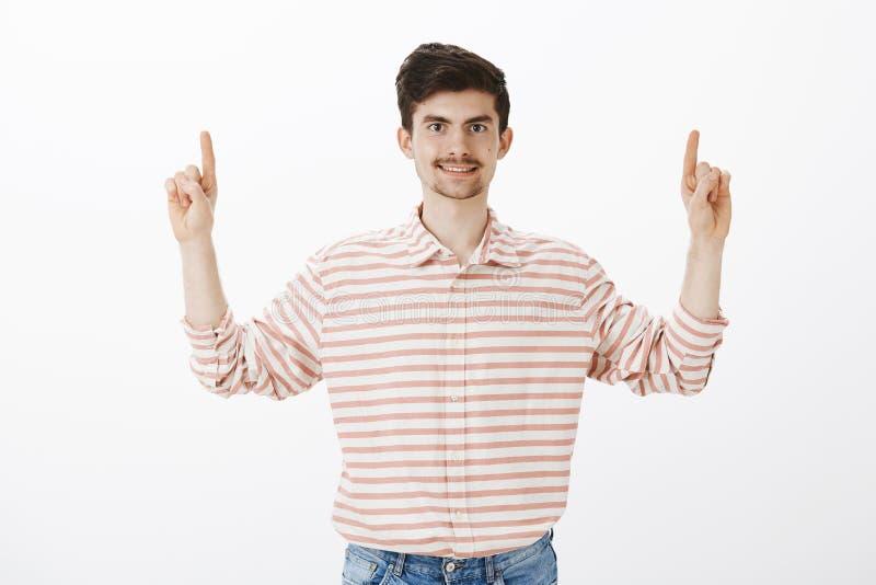 El estudio tiró de individuo ordinario de amistoso-mirada contento en camisa rayada, aumentando los dedos índices y destacando, s imagen de archivo libre de regalías