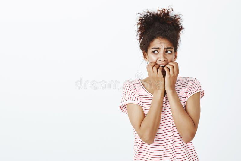 El estudio tiró de mujer rizado-cabelluda insegura asustada en la camiseta rayada, uñas penetrantes, frunciendo el ceño y mirando imagen de archivo libre de regalías