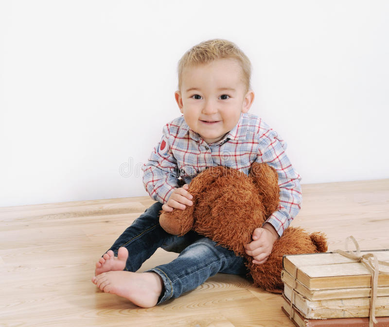 El estudio tiró de pequeño muchacho sonriente lindo con su juguete y libros fotografía de archivo libre de regalías