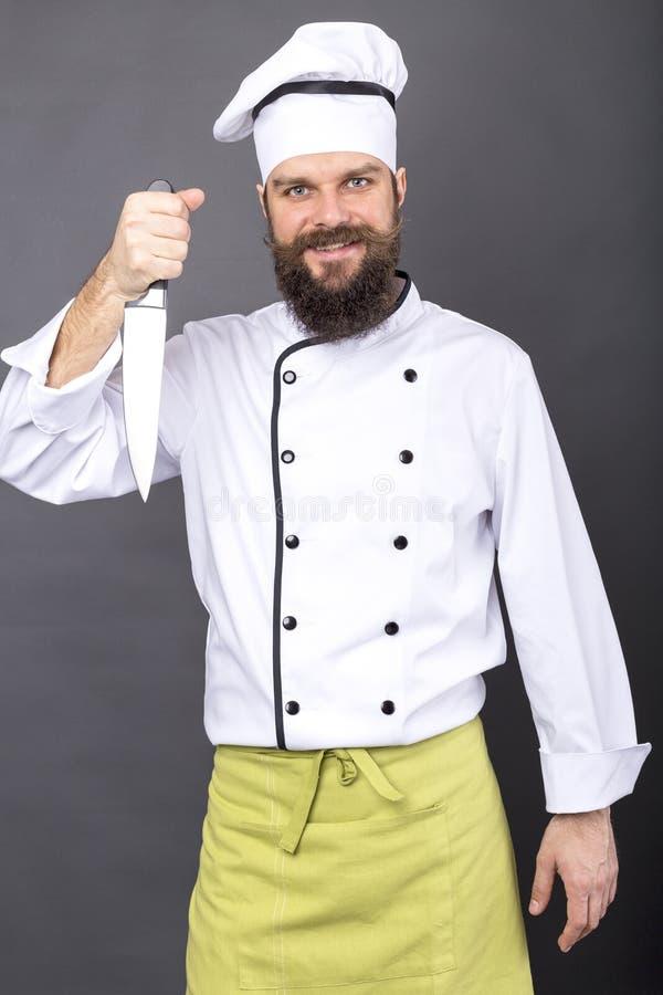 El estudio tiró de un cocinero barbudo que sostenía un cuchillo afilado grande imagen de archivo