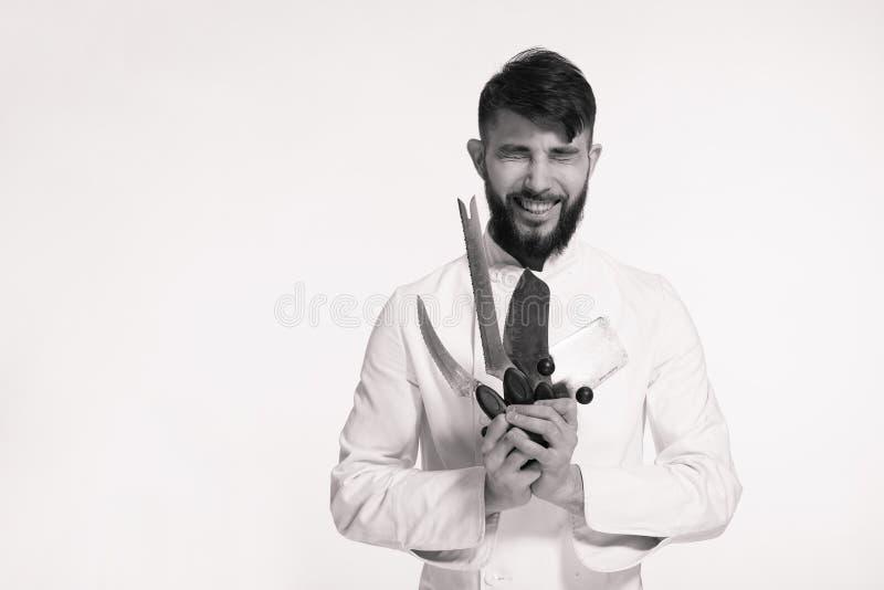 El estudio tiró de un cocinero joven barbudo feliz que sostenía los cuchillos afilados o imagen de archivo libre de regalías