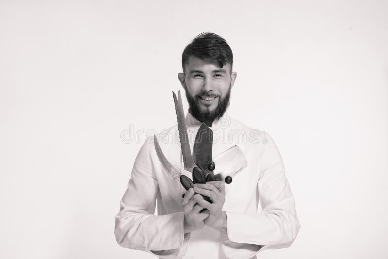 El estudio tiró de un cocinero joven barbudo feliz que sostenía los cuchillos afilados o fotografía de archivo libre de regalías