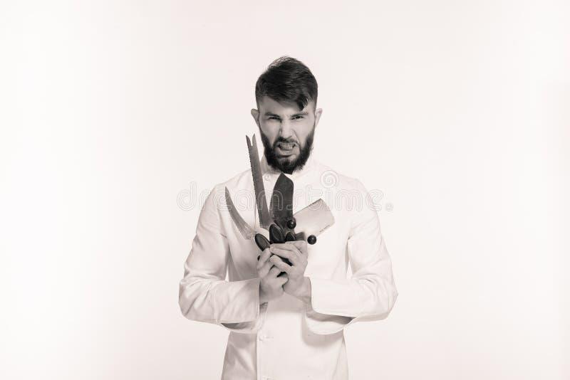 El estudio tiró de un cocinero joven barbudo feliz que sostenía los cuchillos afilados sobre el fondo blanco Cocinero con el cuch foto de archivo libre de regalías
