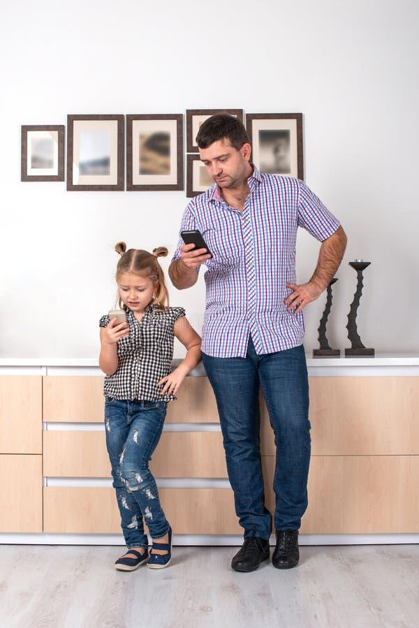 El estudio tiró de una hija y de la colocación en casa y de escribir al mensaje en el teléfono móvil la misma manera La hija la i imagen de archivo libre de regalías