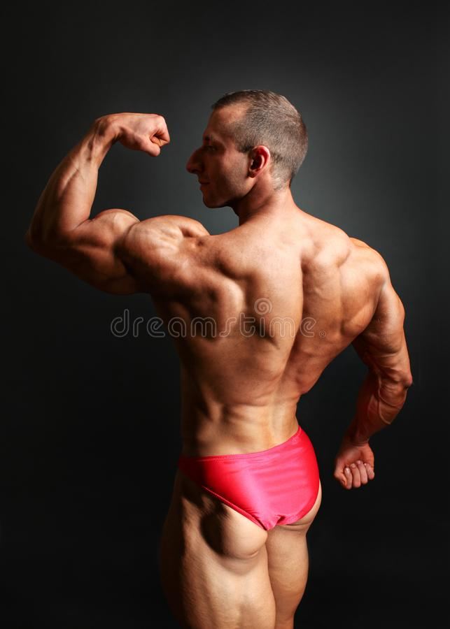 El estudio tiró del culturista masculino joven que presentaba, mostrando su bíceps fotografía de archivo libre de regalías