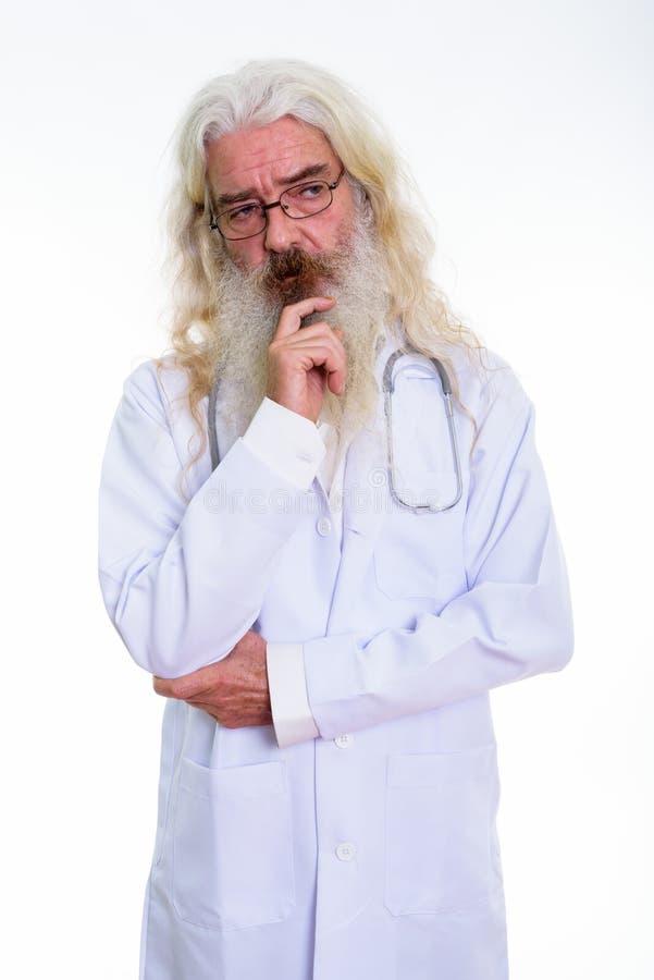 El estudio tiró del doctor barbudo mayor del hombre que pensaba mientras que miraba imagen de archivo libre de regalías