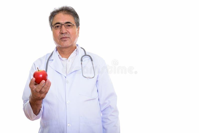 El estudio tiró del doctor persa mayor del hombre que sostenía la manzana roja fotografía de archivo libre de regalías