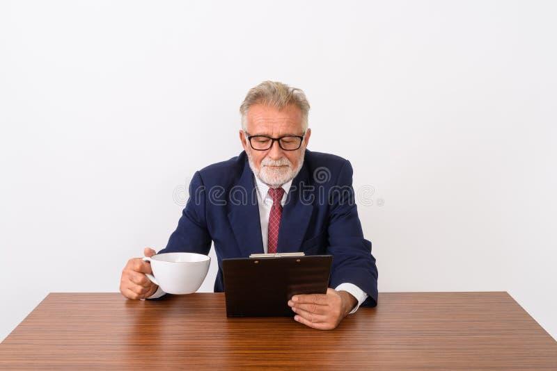 El estudio tiró del hombre de negocios barbudo mayor hermoso que llevaba a cabo el coffe fotografía de archivo